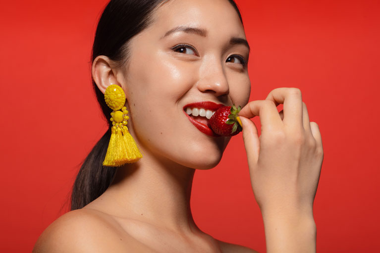 A women with V shape face eating strawberry
